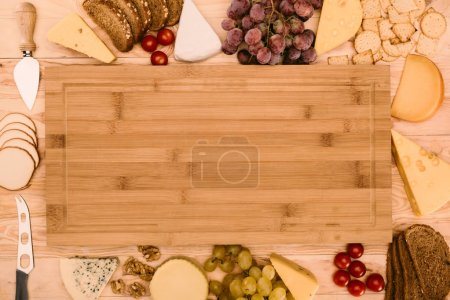 Photo for Top view of arranged types of cheese, grapes, bread, cherry tomatoes and empty cutting board - Royalty Free Image