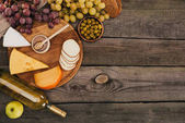 bottle of wine and cheese on cutting board