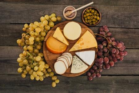 Photo for Flat lay of assortment of cheese types on cutting board, grapes, honey and olives on wooden surface - Royalty Free Image