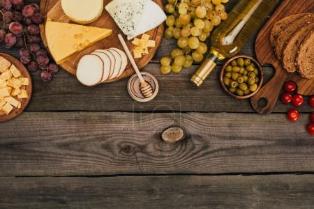 Photo for Flat lay with various types of cheese on cutting board, honey, bread, olives and bottle of wine on wooden tabletop - Royalty Free Image