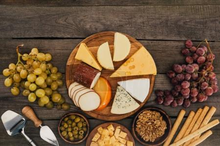 Photo for Top view of arranged various types of cheese on cutting board, olives, hazelnuts and grapes on wooden surface - Royalty Free Image