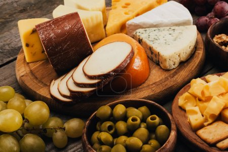 Photo for Close up view of assortment of cheese on wooden cutting board, olives and grapes near by - Royalty Free Image