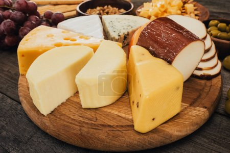 Photo for Close up view of assortment of cheese on wooden cutting board - Royalty Free Image