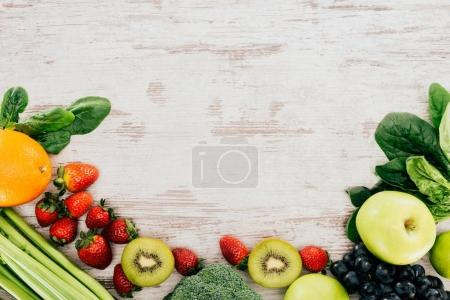 Photo for Top view of arranged organic strawberries, vegetables and fruits on wooden tabletop - Royalty Free Image