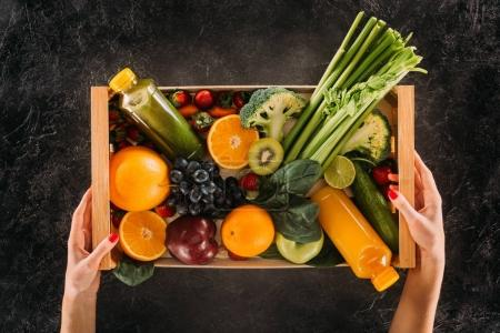 Photo for Partial view of woman holding wooden box with healthy vegetables, fruits and detox drinks - Royalty Free Image