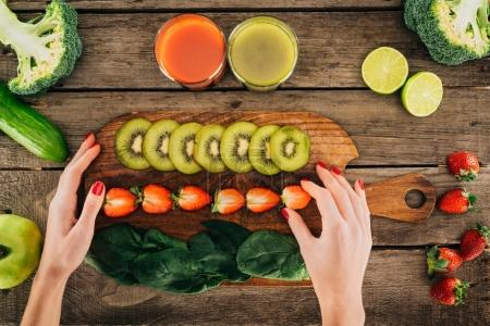 Photo for Partial view of woman holding cutting board with fresh vegetables and fruits - Royalty Free Image