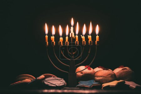 Photo for Traditional jewish menorah for hanukkah celebration, doughnuts and cookies,  isolated on black - Royalty Free Image