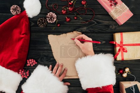 Photo for Cropped view of Santa claus writing present list on wooden tabletop - Royalty Free Image