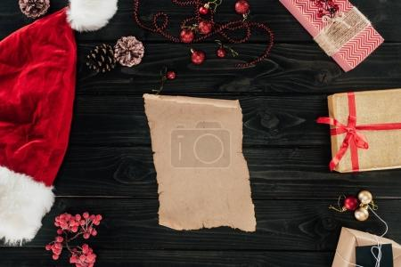 Photo for Top view of blank papyrus, christmas presents and santa hat on wooden tabletop - Royalty Free Image