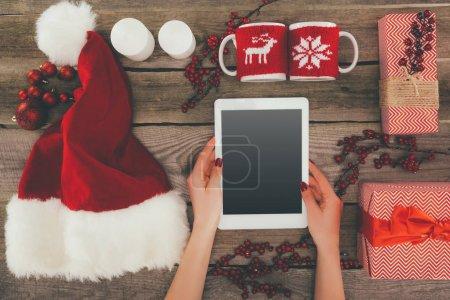 Foto de Recorta la vista del sombrero de Santa, adornos navideños y las manos con tableta digital con espacio de copia en el tablero de madera - Imagen libre de derechos
