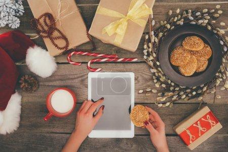 Foto de Vista recortada de regalos de Navidad y las manos con tableta digital con espacio de copia en el tablero de madera - Imagen libre de derechos