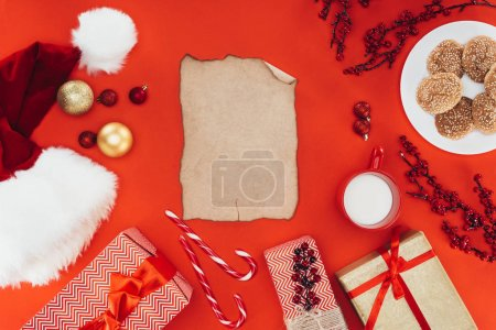 Photo for Top view of blank papyrus, christmas decorations, santa hat and presents, isolated on red - Royalty Free Image