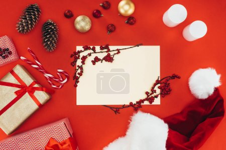 Photo for Top view of blank card, presents and christmas decorations, isolated on red - Royalty Free Image
