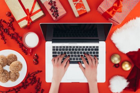 Photo for Cropped view of woman using laptop with copy space at christmastime, isolated on red - Royalty Free Image