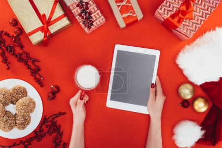 Photo for Top view of christmas gifts, cookies, hands with digital tablet and cup of milk, isolated on red - Royalty Free Image