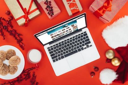 Photo for Flat lay with laptop with amazon website, on red with christmas gifts - Royalty Free Image