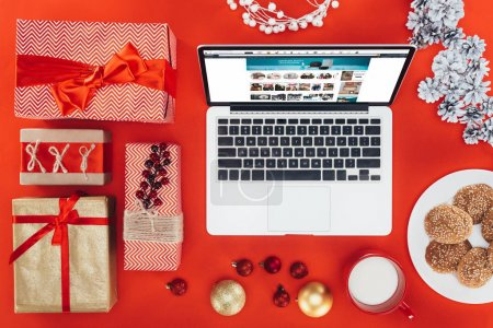 Photo for Flat lay with gifts, laptop with amazon website at christmastime, isolated on red - Royalty Free Image