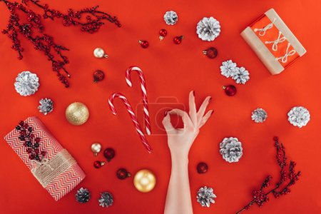 Photo for Cropped view of female hand with ok sign and decorations, candy canes at christmastime, isolated on red - Royalty Free Image