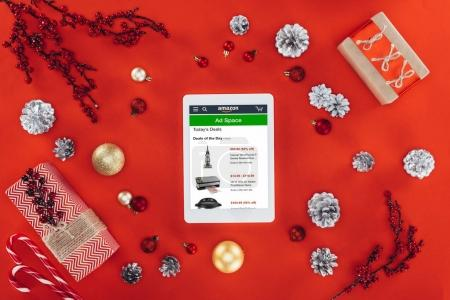 Photo for Top view of digital tablet with amazon website, christmas decor and presents, isolated on red - Royalty Free Image