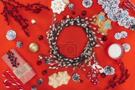 Foto de Vista superior de la corona de Navidad, galletas de jengibre y de regalo, aislado en rojo - Imagen libre de derechos