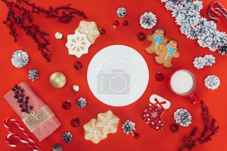 Photo for Top view of christmas decoration, gingerbread cookies and plate with copy space, isolated on red - Royalty Free Image