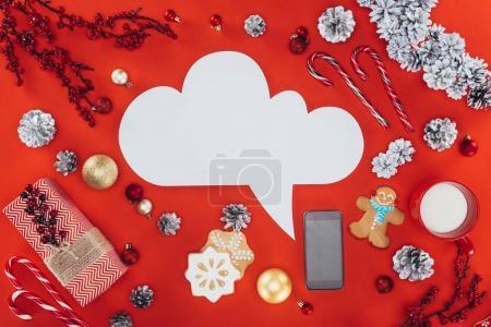 Foto de Bocadillo de diálogo en blanco, decoraciones de Navidad, galletas de jengibre y smartphone, aislado en rojo - Imagen libre de derechos