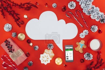 Photo for Blank speech bubble, christmas decorations, gingerbread cookies and smartphone with amazon website, isolated on red - Royalty Free Image