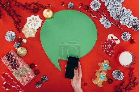 Foto de Vista recortada de la mano con smartphone, bocadillo de diálogo verde, adornos navideños y galletas de jengibre, aisladas en rojo - Imagen libre de derechos