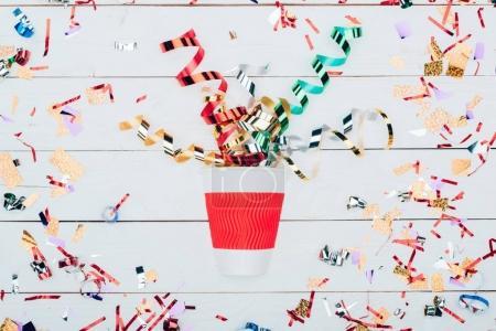 Photo pour Vue de dessus de confettis répandre hors de la tasse de papier sur une table en bois blanc - image libre de droit