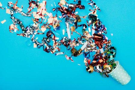Photo pour Vue de dessus de confettis échappe de gobelet en papier sur la surface bleue - image libre de droit