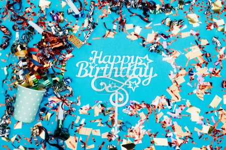 Photo for Top view of happy birthday sign surrounded with confetti isolated on blue - Royalty Free Image