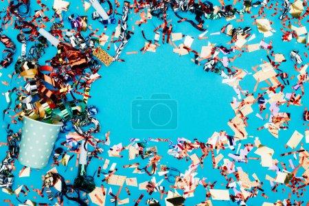 Photo pour Vue de dessus du cadre en confettis avec gobelet jetable isolé sur bleu - image libre de droit