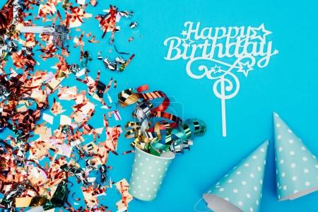 Photo for Top view of birthday confetti with paper cup and party hats on blue tabletop - Royalty Free Image