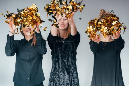 Photo for Group of young women throwing up golden confetti, isolated on grey - Royalty Free Image