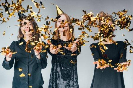 Photo pour Groupe de jolies jeunes femmes vomissant confettis dorés, isolé sur gris - image libre de droit