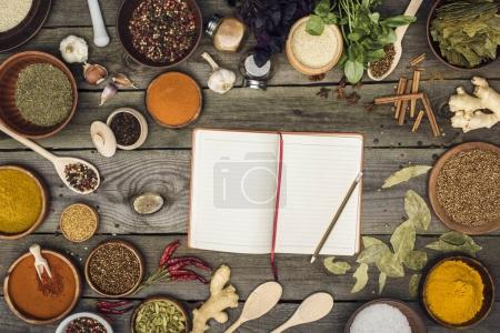 Photo for Top view of notebook for recipes with spices on a table - Royalty Free Image