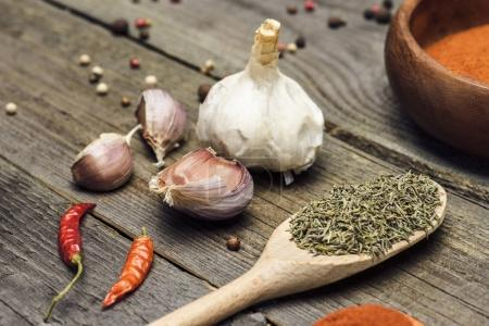 Photo for Wooden ladle with rosemary and garlic on a wooden table - Royalty Free Image