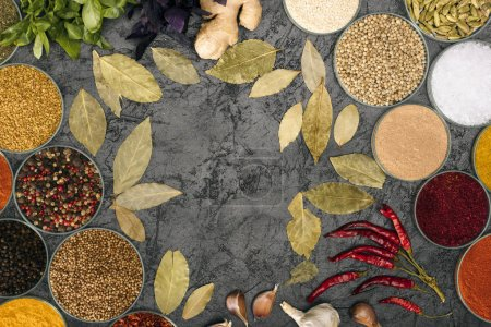 spices in bowls and scattered bay leaves