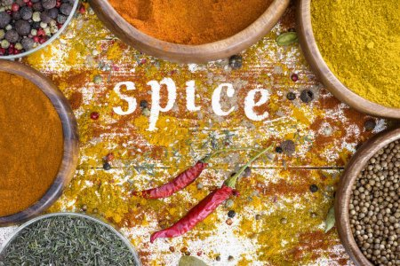 Photo for Top view on scattered spices on table with wooden bowls and word Spice - Royalty Free Image