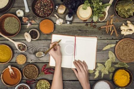 Photo for Cropped image of woman writing down recipe on a wooden table - Royalty Free Image