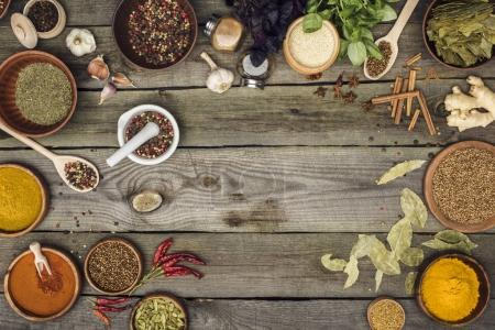 Photo for Top view of different spices and herbs on a gray wooden table - Royalty Free Image