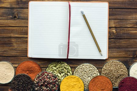 Photo for Top view of notebook for recipes with pencil and spices on a wooden tabletop - Royalty Free Image