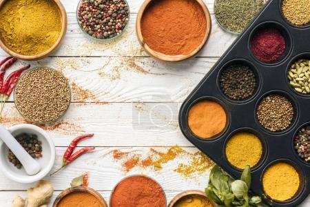 Photo for Top view of scattered spices and glasses with spices on a white tabletop - Royalty Free Image