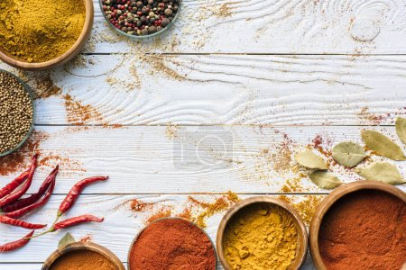 Photo for Top view of scattered spices and glasses with spices on a white surface - Royalty Free Image