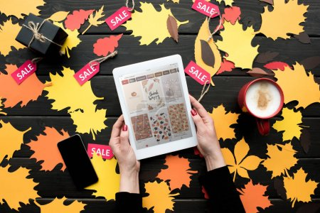 Photo for Cropped view of female hands with digital tablet with pinterest website on table with autumn leaves, coffee and sale tags - Royalty Free Image