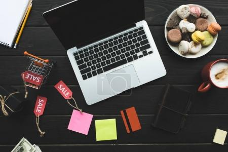 Photo for Top view of laptop and credit card on table with macarons, coffee, little shopping cart and sale tags - Royalty Free Image