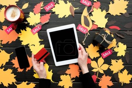 Photo for Cropped view of female hands with digital tablet and credit card on table with autumn leaves, coffee and sale tags - Royalty Free Image