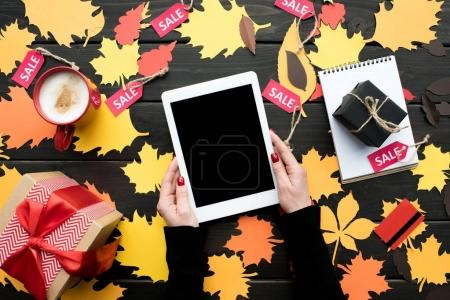 Photo for Cropped view of female hands holding digital tablet on table with autumn leaves, coffee, presents and sale tags - Royalty Free Image