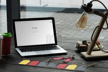Photo pour Ordinateur portable avec google site sur table avec des tags macarons, café et vente de café - image libre de droit