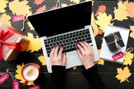 Photo pour Vue de dessus des mains avec ordinateur portable sur la table avec les balises de feuillage, de cadeaux, de café et de vente papier - image libre de droit